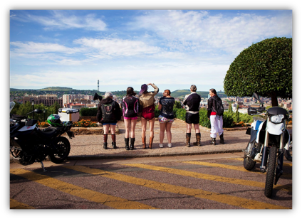 Description: A group of people riding a motorcycle down a dirt road  Description generated with very high confidence