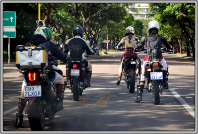 Description: A group of police officers riding on the back of a motorcycle  Description generated with very high confidence