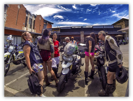 Description: A group of people standing around a motorcycle  Description generated with very high confidence